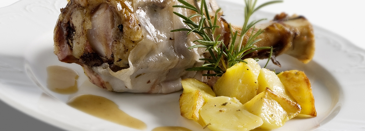 Stinco di maiale lardellato alle erbe con purea di patate e fagioli